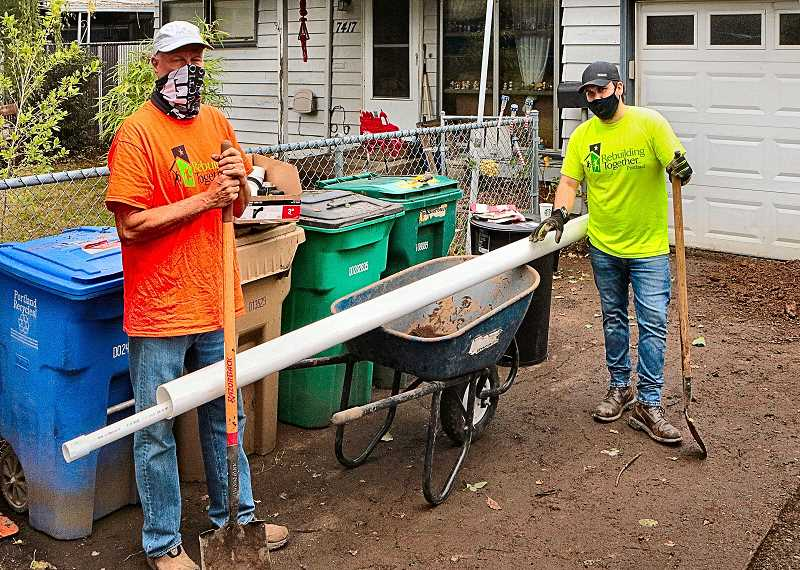 DAVID F. ASHTON - Volunteers pitching in at this Rebuilding Together Portland volunteer site in Mt. Scott-Arleta pause for a group photo in the driveway of a home that had been completely overgrown with vegetation when they arrived.