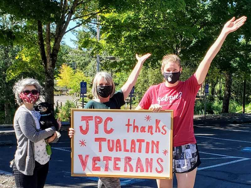 COURTESY PHOTO: CITY OF TUALATIN - Marilyn Brault-Binaghi, left, a Juanita Pohl Center program specialist; her dog Basil; Barb Blub, a center fitness and wellness instructor; and Sara Shepherd, center supervisor, pay tribute to local veterans. Although formal celebrations have been canceled in Tualatin this year due to COVID-19, veterans can receive a front yard sign honoring them for serving their country.