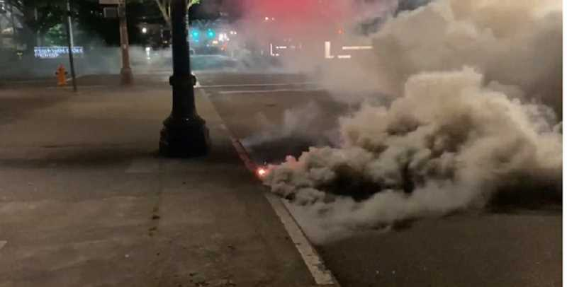 SCREENSHOT - Video footage captured by a protester shows an HC smoke grenade letting out a large cloud of thick gray smoke from a curb in downtown Portland in late July. Protesters and researchers have documented federal agents using the HC smoke grenades, but the Department of Homeland Security left them out of its list of weapons deployed.
