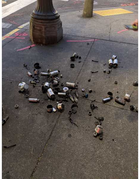 PMG PHOTO: COURTNEY VAUGHN - A pile of spent munition canisters and fragments is dumped on a sidewalk near the Multnomah County Justice Center in downtown Portland on July 22. Protesters and researchers have been collecting detonated canisters and grenades to track which weapons are being used by police.