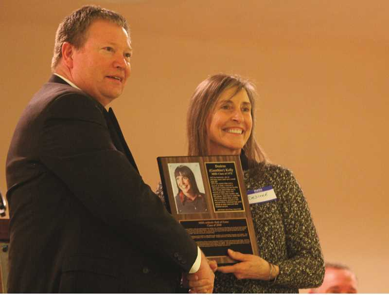 MADRAS PIONEER FILE PHOTO  - Evan Brown, left, inducting Desiree (Gauthier) Kelly into the MHS Athletic Hall of Fame in January. Brown and former MHS athletic director Margaret Sturza kickstarted the hall idea, and it has so far honored 29 athletes, teams and coaches from the 1950s through the 2000s.