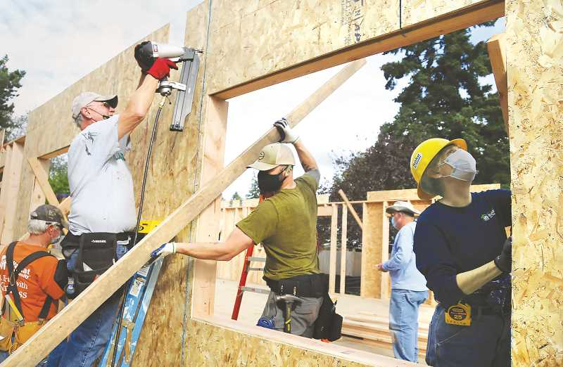 PMG PHOTO: GARY ALLEN - A cadre of volunteers raise and secure the walls of a duplex Habitat for Humanity is constructing on Fifth Street in Newberg.