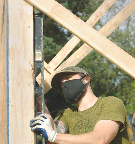 PMG PHOTO: GARY ALLEN - Jared Logan, a volunteer from Aloha, checks plum on a wall erected on the Habitat for Humanity home on Fifth Street in Newberg.
