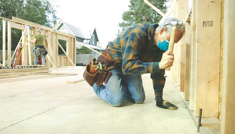 PMG PHOTO: GARY ALLEN - Habitat volunteer Lowell Davis secures a wall to the sill at the organization's latest build.