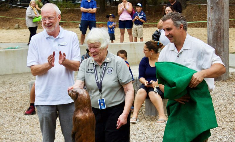 PMG FILE PHOTO - Gresham Councilor David Widmark, Joan Albertson and artist Rip Caswell unveil the otter statue at Nadaka Nature Park.