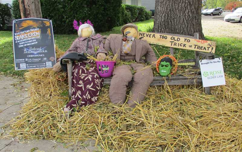 PMG PHOTO: DEBORAH GUINTHER - These scarecrows from Rose Elder Law enjoy some hay treats.