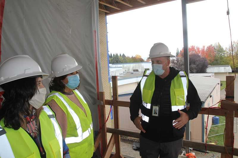 PMG PHOTO: JUSTIN MUCH - Woodburn School District Director of Safety and Operations Casey Woolley, right, explains construction details to WSD Board members Linda Reeves and Noemi Legaspi during a walk through at the Lincoln Elementary and French Prairie Middle schools on Friday, Oct. 23.