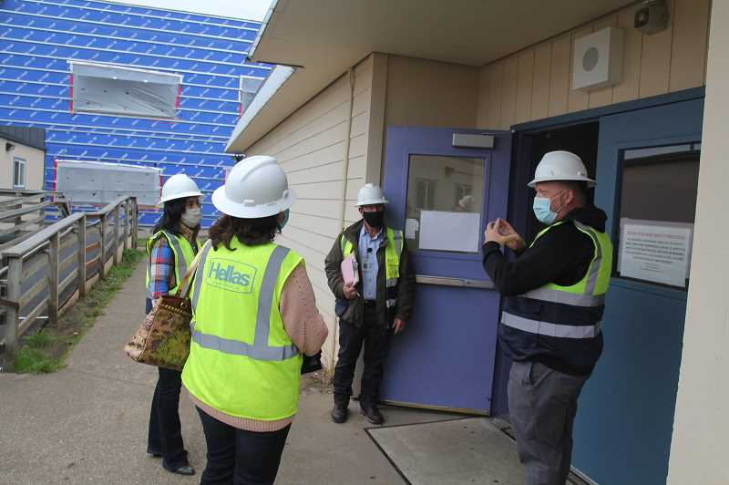 PMG PHOTO: JUSTIN MUCH - Woodburn School District Director of Safety and Operations Casey Woolley, right, and Ivan Leigh, center, explain construction details to WSD Board members Linda Reeves and Noemi Legaspi during a walk through at the Lincoln Elementary and French Prairie Middle schools on Friday, Oct. 23.