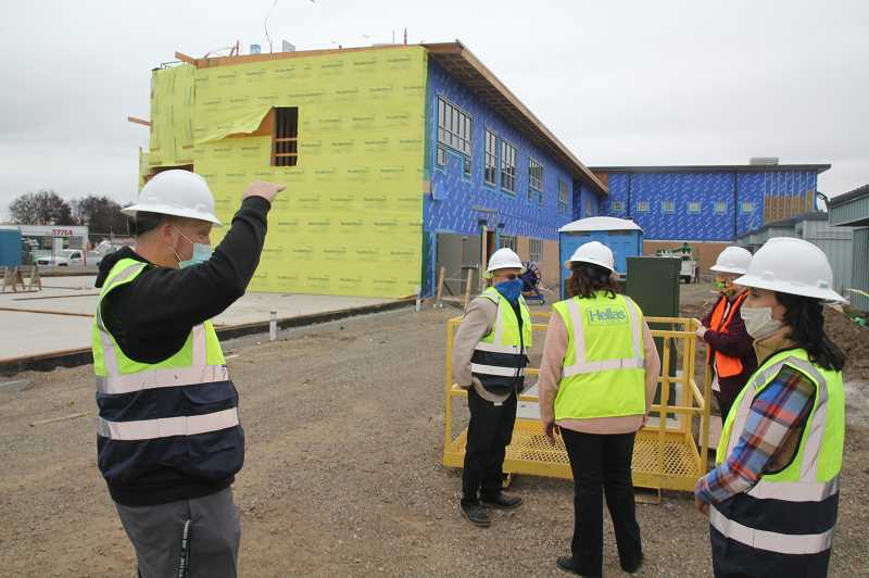 PMG PHOTO: JUSTIN MUCH - Woodburn School District Director of Safety and Operations Casey Woolley, left, leads a walk through of construction improvements ongoing at Nellie Muir Elementary School on Friday, Oct. 23.