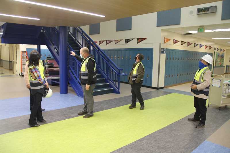 PMG PHOTO: JUSTIN MUCH - Woodburn School District Director of Safety and Operations Casey Woolley, center, and Ivan Leigh explain some of the construction improvements at Valor Middle School to WSD Board members Linda Reeves, Noemi Legaspi and WSD Superintendent Oscar Moreno Gilson, right