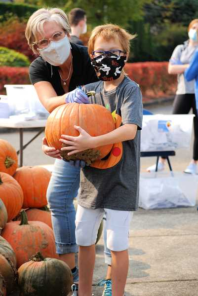 COURTESY PHOTO: TUALATIN TOGETHER - Skyler, a Tualatin Elementary School student, wrestles with a pumpkin on Oct. 7, provided by Tualatin Togethers  Gratitude Pumpkin Package.