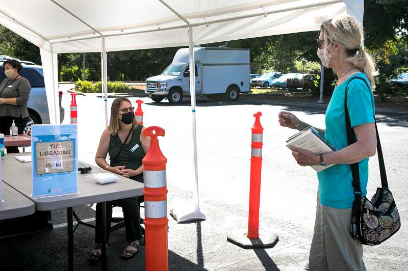 FILE PHOTO: JAIME VALDEZ - Ann-Marie Anderson, left, helps a patron with a book on hold in an outdoor covered area at the Tigard Public Library in August. If approved by the Washington County Board of Commissioners on Nov. 3, all fines on overdue library materials would be eliminated.