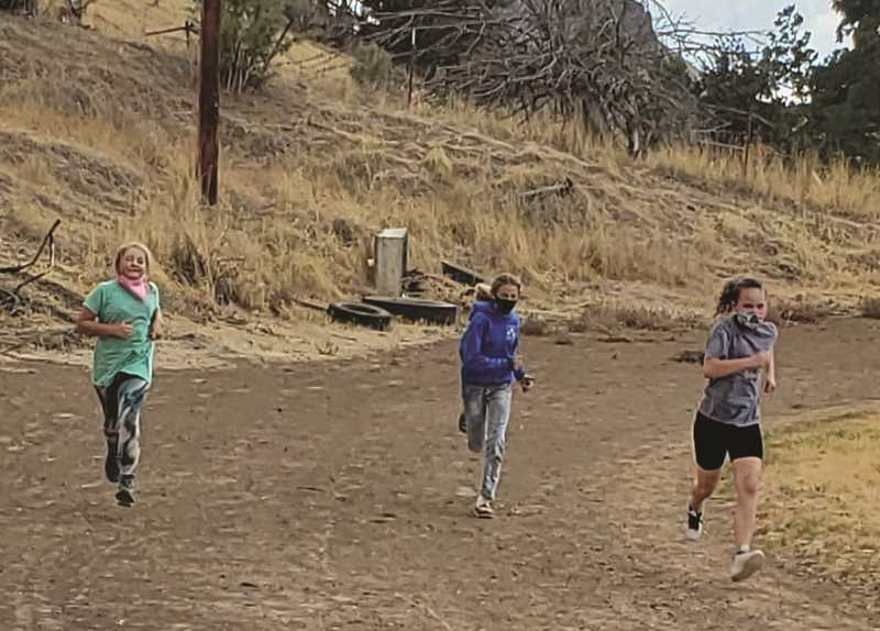 PHOTO SUBMITTED BY JACKI MILLER - Mitchell School students trot around the track during a walk-a-thon to raise money for wildfire victims in Mill City.