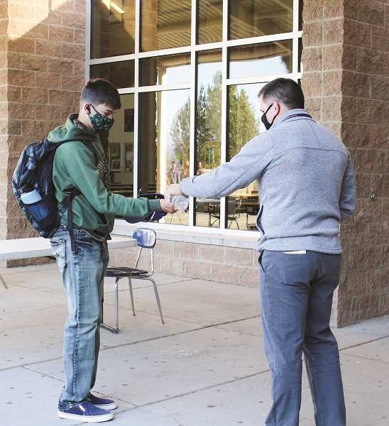 CENTRAL OREGONIAN - A Crook County High School student is given some hand sanitizer on his way into the building. This is one of several safety measures now in place at the schools to prevent the spread of COVID-19.