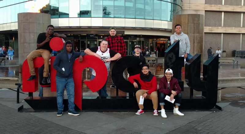 COURTESY OF SQUIRES PDX - From left:  Kwame Assuman, Qayyum Jackson, Shanne Sowards, Brian Santana, Ryan Heitzenrate, David Ortiz, Johnathan Ortiz and Danny Vazquez pose for a photo in front of the Moda Center before of an outing to a Portland Trail Blazers game. Squires outings are intended to give these young fathers an opportunity to blow off some steam, talk about what's going on in their lives and connect with others with similar experiences.