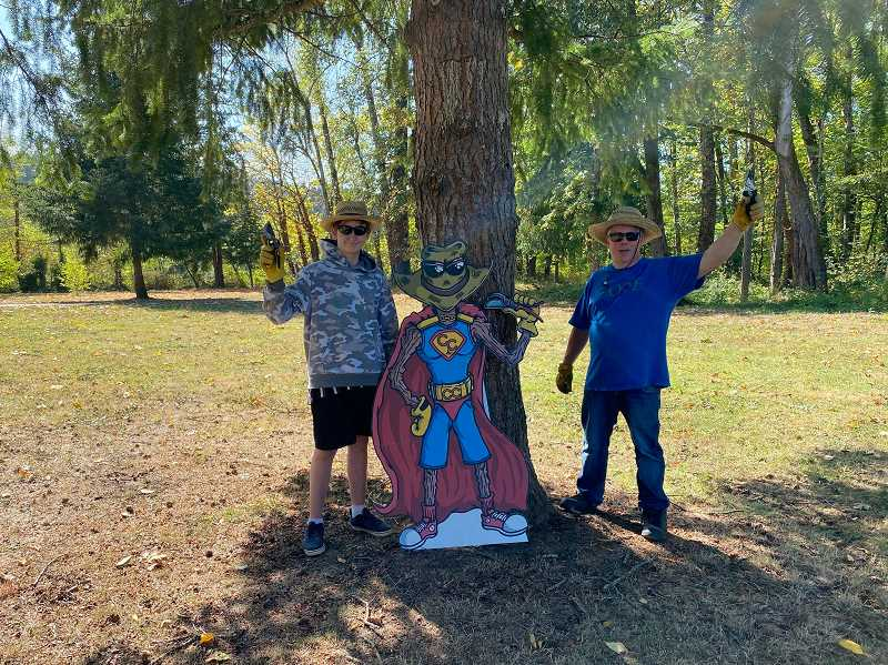 COURTESY PHOTO - Monte Harris, right, and his girlfriend's grandson Isaac stand with an environmental superhero called Clyde the Climate Crusader, based on Harris wearing a hat, gloves and sunglasses for park cleanups.