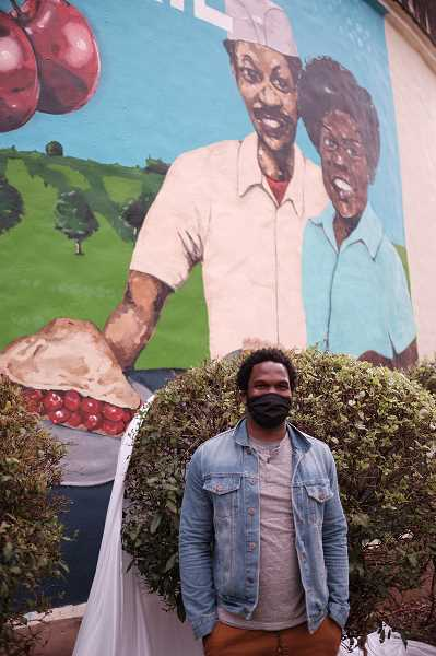 COURTESY PHOTO: HAMID SHIBATA BENNETT - Mural artist Jeremy Okai Davis stands in front of his public art near Water Tower Park in Milwaukie.