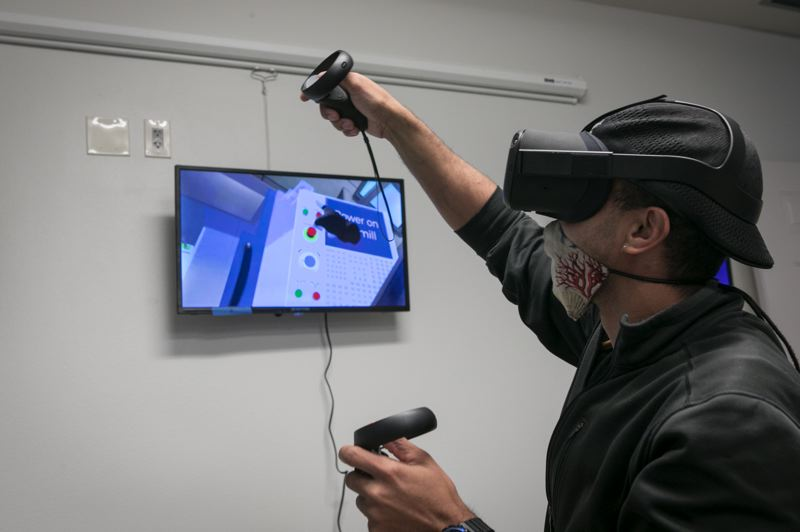 PMG: JAIME VALDEZ - Isaac ForehandIsaac Forehand, Application Developer at Ineality LLC, demonstrating virtual reality using an Oculus Quest 2 headset. The dark hand can press buttons and turn objects but it not as manipulative as a human hand.