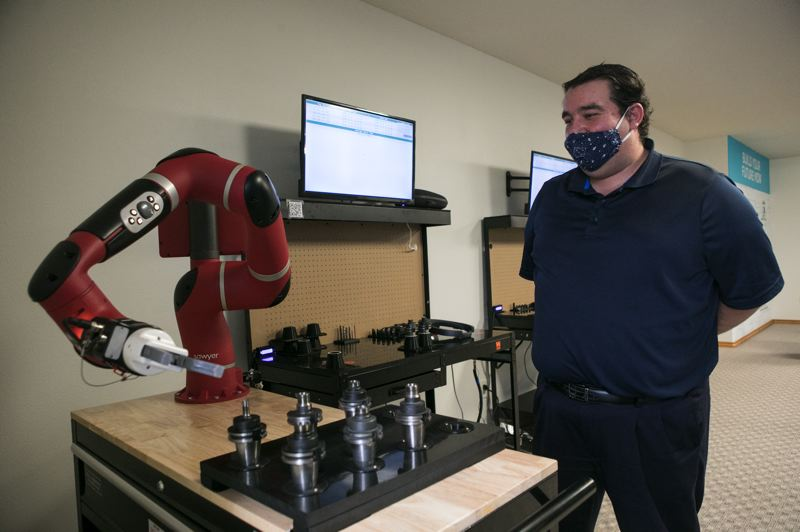 PMG: JAIME VALDEZ - Jason Stratton, Manufacturing Consultant, OMEP, demonstrating a cobot, which is designed to work safely alongside humans.