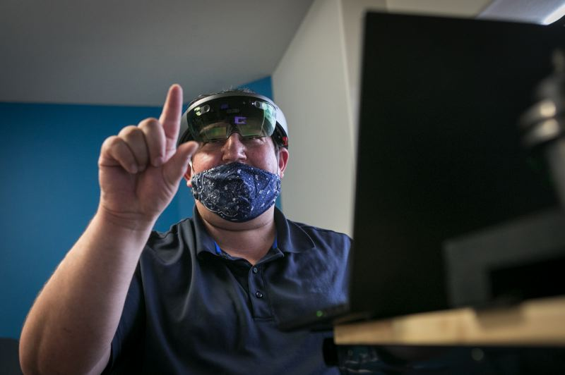 PMG: JAIME VALDEZ - Jason Stratton, Manufacturing Consultant, OMEP, demonstrating augmented reality using a Microsoft HoloLens headset. The set allows for quicker training on traditional machines, providing exploded views of parts and allowing for note taking.