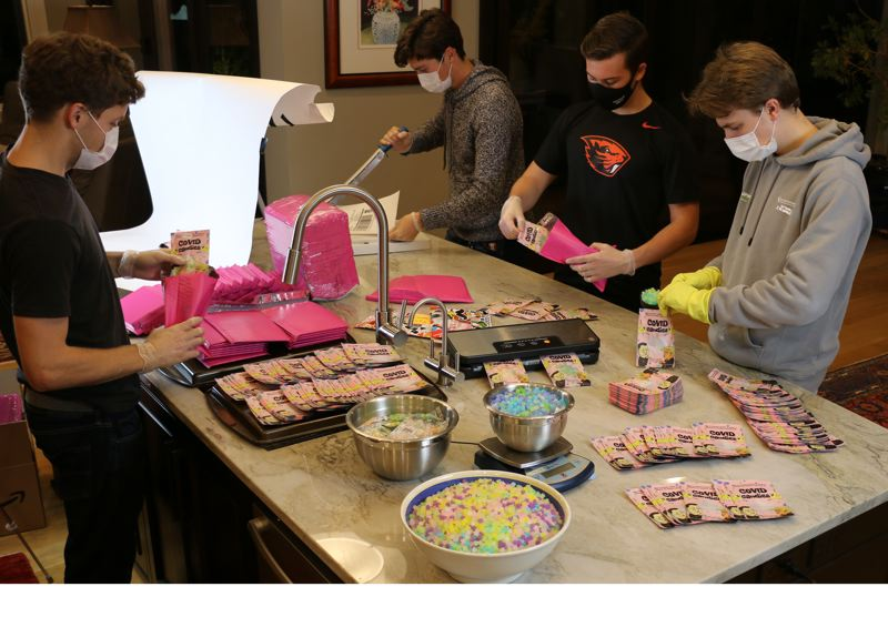 COURTESY: HUDSON HALE - COVID Candies being packaged by the friends of high schooler udson Hale (operating paper cutter). Profits from the $12 a bag sweets, which look like coronaviruses, will go to charity.