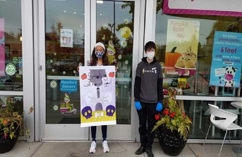COURTESY PHOTO - Middle school student Flora Martinez and Menchie's employee Taylor Robbins hold up a Halloween poster outside the frozen yogurt parlor.
