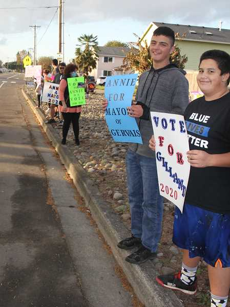 PMG PHOTO: JUSTIN MUCH - Dozens of sign-wielding Gervais residents lined both sides of Douglas Avenue Friday evening to encourage people to vote.