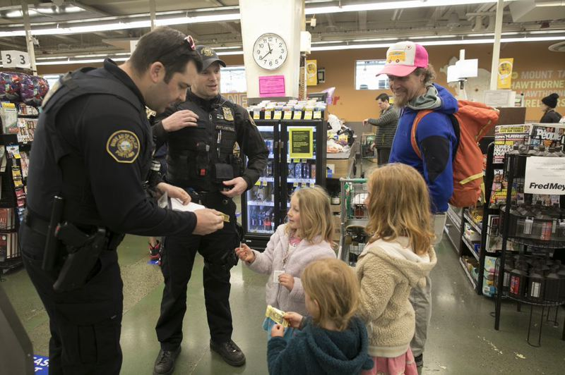 PMG PHOTO' JAIME VALDEZ - Mathew Jacobsen, left, and Shaun Sully, both police officers with the Portland Police Bureau Neighborhood Response Team, visit with a family in Fred Meyer along Southeast Hawthorne Boulevard.