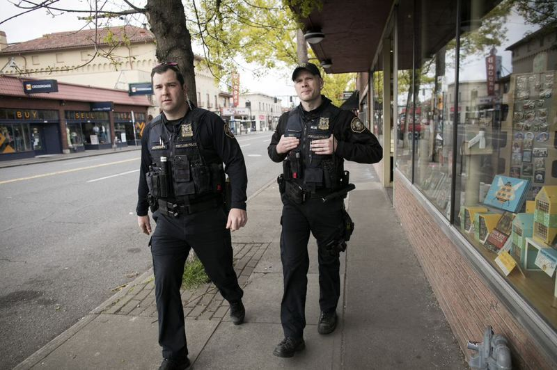 PMG FILE PHOTO - Mathew Jacobsen, left, and Shaun Sully, both police officers with the Portland Police Bureau Neighborhood Response Team, check on businesses along Southeast Hawthorne Boulevard.