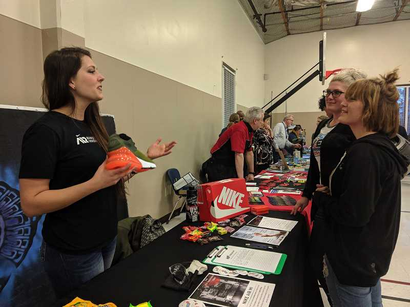 PMG FILE PHOTO - Jess Lindener of Nike talks to Taiylor Tarrant and Carina Kauffman about Nikes expanding manufacturing plant during a career fair in Beaverton last year. Nike filed notice with the city, state and county this month that it will eliminate at least 700 jobs at its world headquarters.