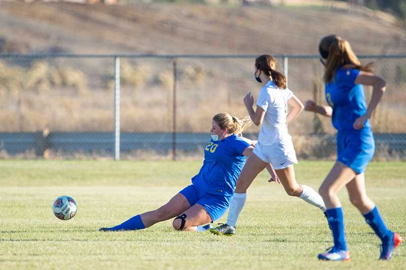 LON AUSTIN - Emma Bales, 20, slide-tackles a ball during the Cowgirls' 7-0 loss to Sisters Oct. 28. The two teams were locked in a  scoreless battle for the first 10 minutes of the game, but Sisters was able to score four before the end of the half.