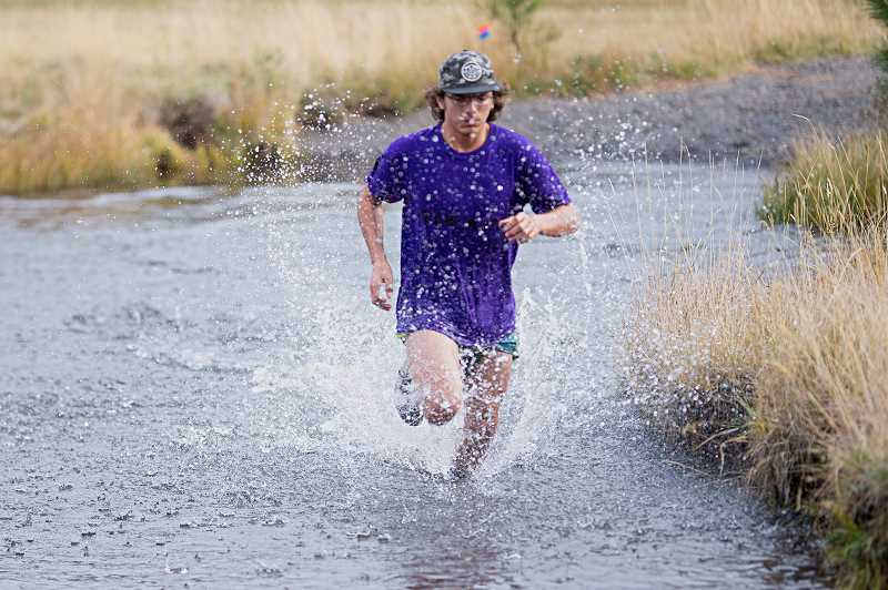 LON AUSTIN - Ilex Vail splashes through the stream during the Sisters event Oct. 30. Vail was one of six Cowboy runners to take part in the relay along with four Cowgirls. CCHS will host several teams Wednesday in a 5K race at Barnes Butte trail system.