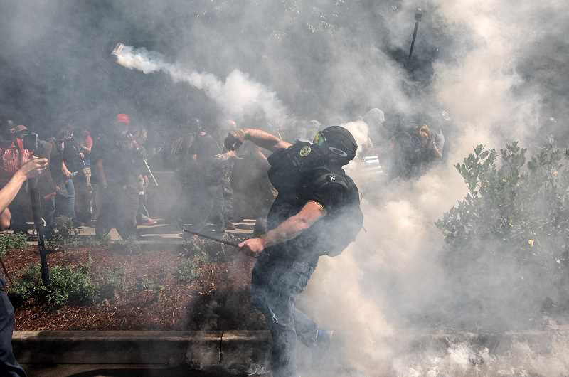 (Image is Clickable Link) PMG PHOTO: JONATHAN HOUSE - A man hurls a smoke bomb during a street brawl in downtown Portland on Saturday, Aug. 22. A new lawsuit alleges local and federal police have discriminated against protesters with disabilities during Black Lives Matter demonstrations in Portland.