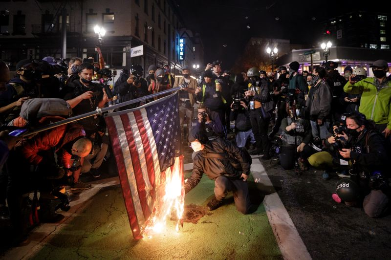 PMG PHOTO: JONATHAN HOUSE - A protester lights an American flag on fire during a demonstration in SW Portland on Wednesday.