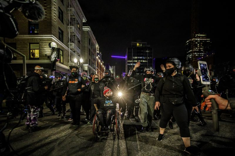 PMG PHOTO: JONATHAN HOUSE - A group of protesters are pushed west of SW Broadway by Unified Command officers during downtown demonstrations on Wednesday evening.