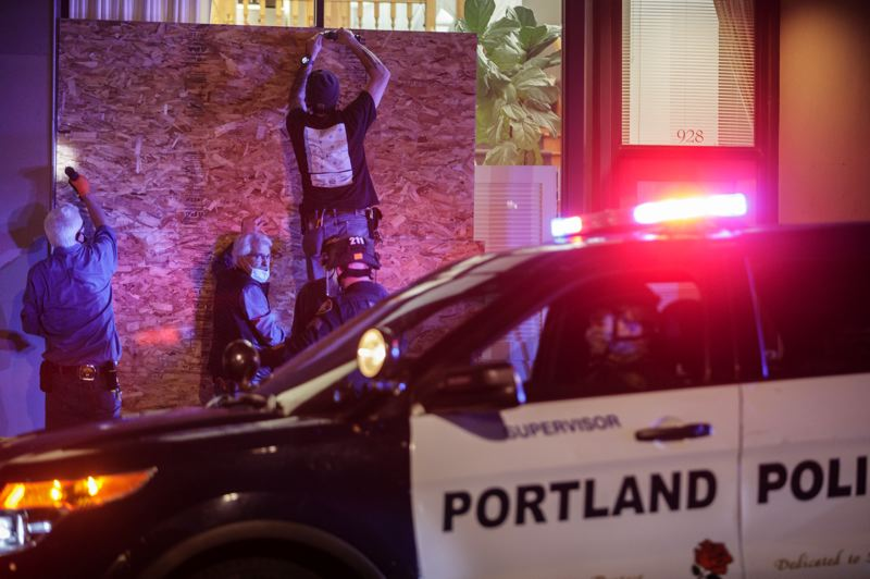 PMG PHOTO: JONATHAN HOUSE - Workers frantically boarded up a downtown business as a protest that had been declared a riot raged nearby in Portland on the evening of Nov. 4.