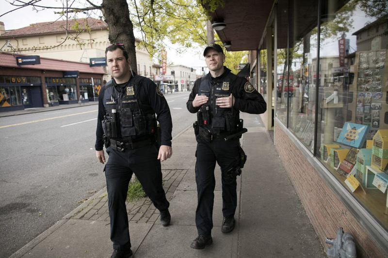PMG FILE PHOTO - Mathew Jacobsen, left, and Shaun Sully, both police officers with the Portland Police Bureau Neighborhood Response Team, shown checking on businesses along Southeast Hawthorne Boulevard.