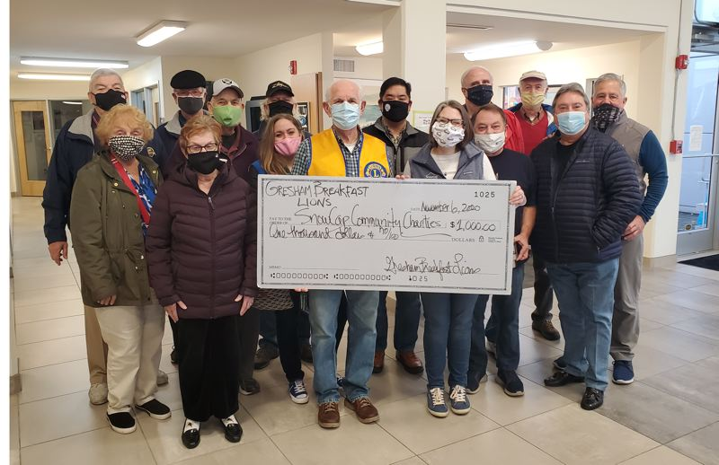 PAMPLIN MEDIA PHOTO - Members of the Gresham Breakfast Lions Club donated $1,000 to SnowCap Community Charities.  Making the donation is Club President Jim Bumgardner, in the yellow vest. SnowCap Executive Director Kirsten Wageman is accepting the donation.
