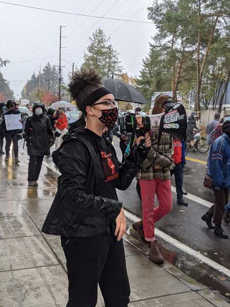 PMG PHOTO: COURTNEY VAUGHN - Keenan Gray leads group chants as a march makes its way down Multnomah Boulevard in Multnomah Village.