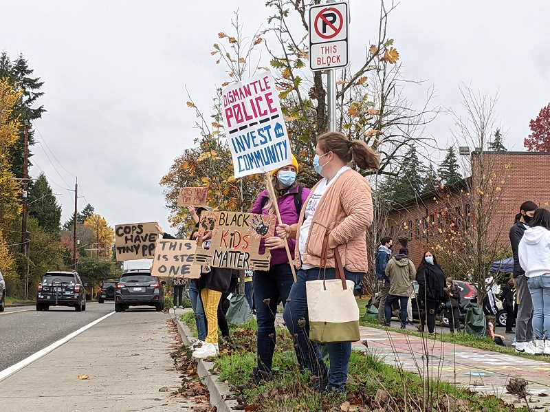 PMG PHOTO: COURTNEY VAUGHN - Demonstrators hold signs along Multnomah Boulevard in Southwest Portland shortly before a massive Black Lives Matter march overtook the street.
