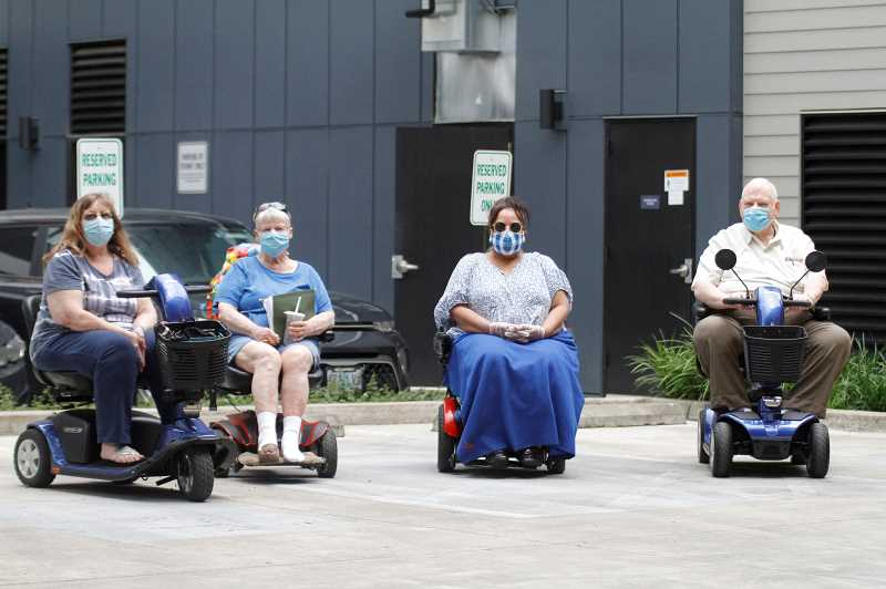PMG PHOTO: WADE EVANSON - Beaverton residents (left to right) Linda Briggs, Lori Stewart, Kim Pettit and David Loucks sit idle in the parking lot at the Barcelona Apartments in Beaverton. Their parking issues have to questions regarding the rule and the spirit of ADA laws.