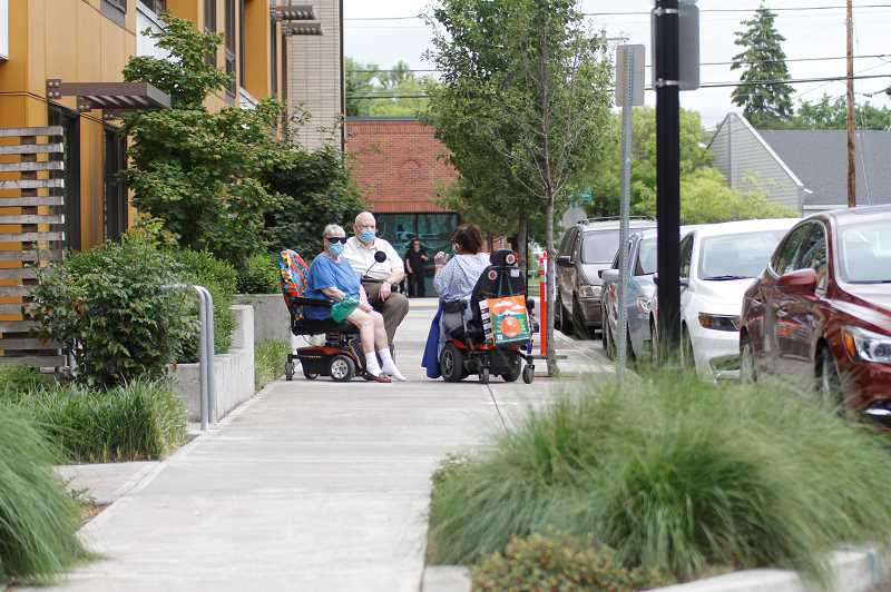 PMG PHOTO: WADE EVANSON - ADA tenants of the Barcelona Apartments in Beaverton gather on the sidewalk behind their units on Second Street.