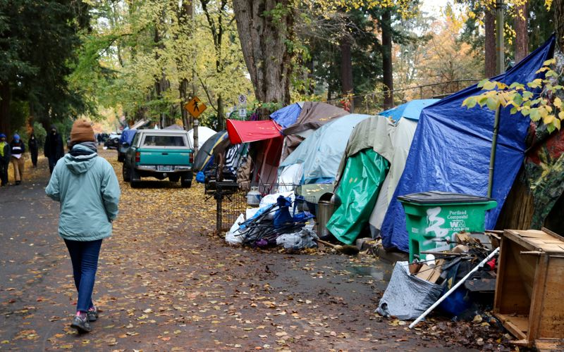 PMG PHOTO: ZANE SPARLING - A person walks past a homeless camp on Southeast Oak Street on the border of Laurelhurst Park in Portland on Tuesday, Nov. 10.