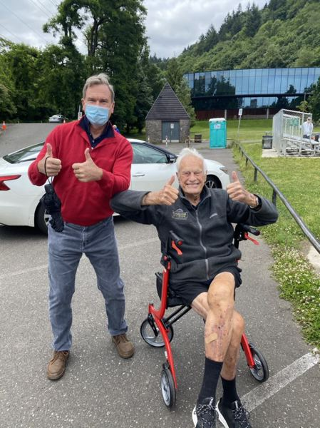 CONTRIBUTED - Leading up to his 100th birthday in August, Bud Lewis (shown with his trainer) navigated his walker more than 100 laps around the Duniway Park track to focus attention on and raise contributions for the Sunshine Division. Donations are still coming in, but to date they are nearing $150,000.