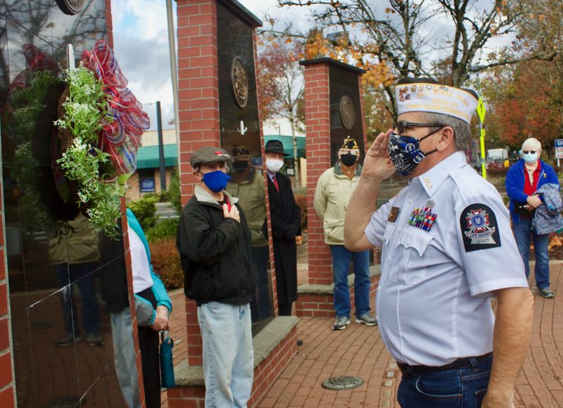PMG PHOTO: CHRISTOPHER KEIZUR - Veteran Frank West hangs a wreath in honor of those who served during a Veterans Day ceremony in Gresham Wednesday morning, Nov. 11.
