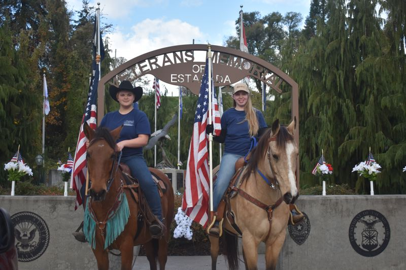 PMG PHOTO: EMILY LINDSTRAND - Amber Haggstrom and Alisha Behrens waved American flags on horseback in honor of Veterans Day on Wednesday, Nov. 11.
