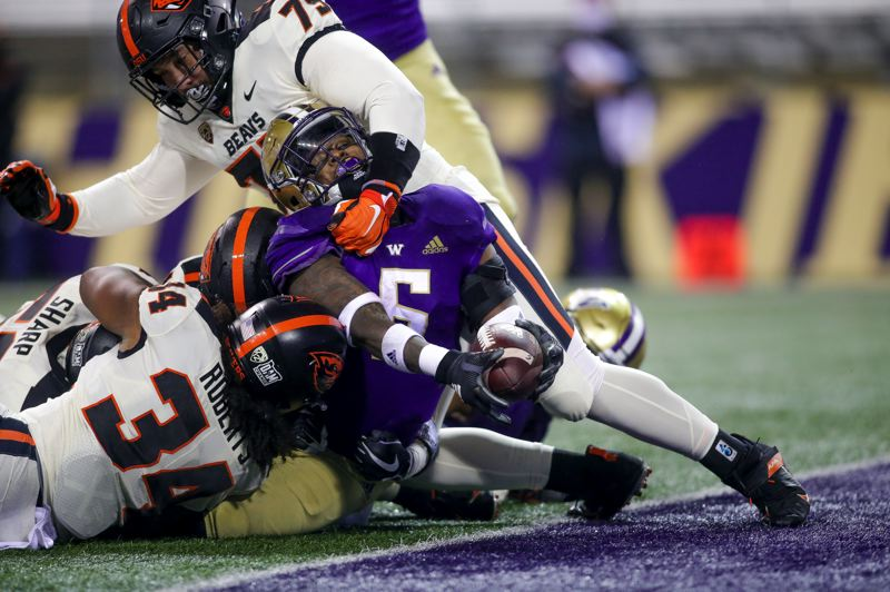 COURTESY PHOTO: UW ATHLETICS - Oregon State's Avery Roberts and Evan Bennett stopped Washington's Richard Newton at the goal line, but the Huskies ran for 267 yards in their 27-21 win Saturday.