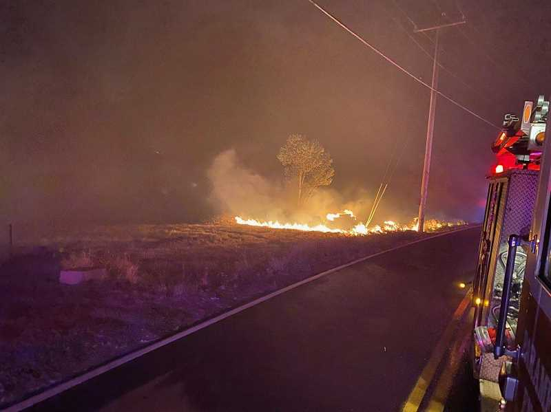 COURTESY LT. RICH STAMPS - Fire burns alongside a road as a fire engine passes at the Chehalem Mountain-Bald Peak fire that was whipped by high winds on Sept. 8.