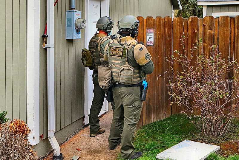 DAVID F. ASHTON - In this training scenario, held at a vacant house near Johnson Creek - when SERT officers hear gunshots coming from the backyard, they cautiously open the fence gate before entering.