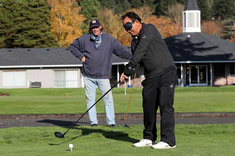 PMG PHOTO: JAIME VALDEZ - Narayan Gurung practices his swing before teeing off at the King City Public Golf Course on Wednesday, Nov. 11. Gurung and his friend Bud played a rematch after a game last summer where he won while blindfolded. He won again on Nov. 11.
